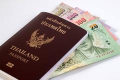 Passaporto tailandese con la banconota tailandese dei soldi isolata su bianco Immagine Stock