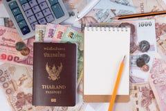 Passaporto tailandese con la banconota tailandese dei soldi, la moneta tailandese e l'aeroplano Fotografia Stock