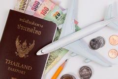 Passaporto tailandese con la banconota tailandese dei soldi, la moneta tailandese e l'aeroplano Immagine Stock
