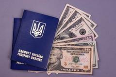 Passaporto ucraino internazionale con i dollari americani isolati su fondo grigio Fotografie Stock Libere da Diritti