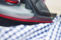 Passar da dona de casa roupa ocasional no close up da tábua de passar a ferro fotografia de stock royalty free