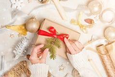 Passatempo criativo As mãos do ` s da mulher envolvem o presente feito a mão do feriado do Natal no papel do ofício com fita da g fotografia de stock