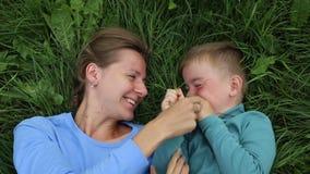 Passatempo di divertimento della madre e del figlio Mamma e bugia di tre anni del figlio sull'erba e divertiresi archivi video