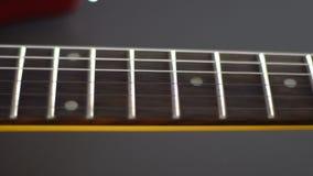 Passe ao longo das cordas em um close-up da guitarra elétrica filme