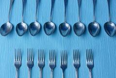 Passe colheres e forquilhas cinzentas em uma tabela azul Imagens de Stock