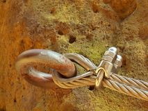 Passe a corda torcida fixada no bloco pelos ganchos instantâneos dos parafusos Detalhe de extremidade da corda ancorado na rocha Imagem de Stock Royalty Free