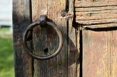 Passe o anel do punho na porta de madeira velha na vila do russo, textura de madeira, fundo Fotografia de Stock Royalty Free
