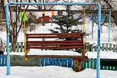 Passe o balanço no campo de jogos no inverno foto de stock