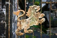 Passe o detalhe oxidado do leão na porta de um templo do Balinese foto de stock