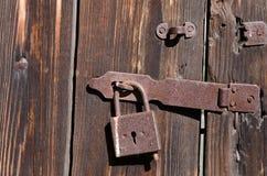 Passe o fechamento na asseguração do metal que pendura na porta de madeira foto de stock royalty free