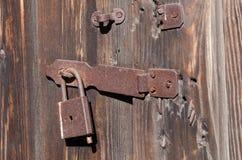 Passe o fechamento na asseguração do metal que pendura na porta de madeira imagens de stock royalty free