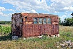 Passe o recipiente oxidado com as janelas no prado na grama Imagens de Stock