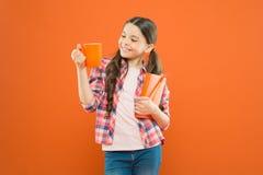 Passe o tempo agradável com livro favorito Copo da posse da menina do ch? e do livro Literatura para crian?as Aprecie passar o te fotos de stock