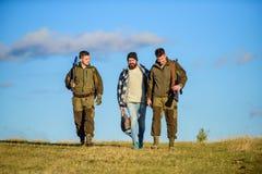 Passe-temps brutal Groupez le ciel bleu de fond de nature de chasseurs ou de garde-chasse d'hommes Les hommes portent des fusils  images stock