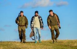 Passe-temps brutal Groupez le ciel bleu de fond de nature de chasseurs ou de garde-chasse d'hommes Types recueillis pour la chass image libre de droits