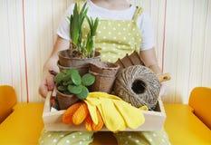 Passe-temps du ` s d'enfants Un petit enfant s'assied sur un banc et tient un plateau avec l'inventaire dans des ses mains Photo libre de droits