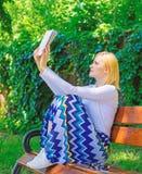 Passe-temps intellectuel La fille reposent le banc détendant avec le livre, fond vert de nature Livre lu occupé de jolie dévoreus image libre de droits