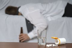 Passed out. Glass of water and pills on the table. In the background out of focus a passed out businessman on the sofa Stock Images