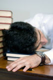 Passed Out. Man in business attire surrounded by books Stock Photos