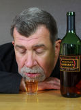 Passed Out Drunk Alcoholic Adult Man. An alcoholic adult man passed out with a Whiskey bottle and shot glass on a bar Royalty Free Stock Images