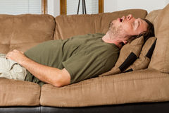 Passed out hard. Man asleep on the couch with his mouth wide open Royalty Free Stock Image