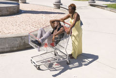 Passed out man. A woman pushes her passed out husband down a walkway in a shopping cart.  Can be used for partying inferences or alcohol inferences Stock Photography