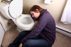 Passed out by toilet. Young woman slumped over toilet bowl stock image