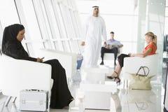 Passeggeri che attendono nel salotto di partenza dell'aeroporto Fotografia Stock