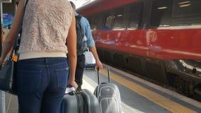 Passeggeri che si avvicinano al treno al punto di vista del binario alla stazione ferroviaria di estremità video d archivio