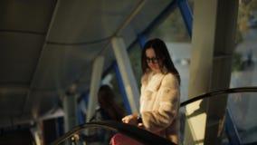 Passeggeri con le valigie che vanno giù facendo uso della scala mobile all'aeroporto video d archivio