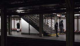 Passeggeri del sottopassaggio che aspettano nel freddo il treno Immagine Stock