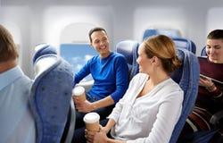 Passeggeri felici con caffè che parlano in aereo immagini stock