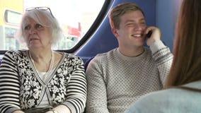 Passeggeri preoccupanti dell'uomo sul viaggio del bus con la telefonata stock footage