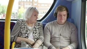 Passeggeri preoccupanti dell'uomo sul viaggio del bus con musica rumorosa stock footage