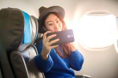 Passeggero asiatico felice che si siede su un aereo vicino alla finestra ed alle prese un selfie sul vostro smartphone immagini stock libere da diritti