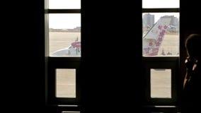 Passeggero che parla sul telefono vicino alla finestra dentro l'aeroporto nella sala di attesa archivi video