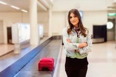 Passeggero della donna in 20s che aspetta i suoi bagagli al nastro trasportatore Immagine Stock