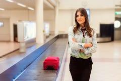 Passeggero della donna in 20s che aspetta i suoi bagagli al nastro trasportatore Fotografia Stock Libera da Diritti