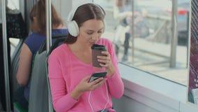 Passeggero della giovane donna che gode del viaggio al trasporto pubblico, sedentesi con le cuffie vicino alla finestra nel tram  video d archivio
