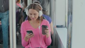 Passeggero della giovane donna che gode del viaggio al trasporto pubblico, sedentesi con le cuffie vicino alla finestra nel tram  archivi video