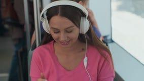 Passeggero della giovane donna che gode del viaggio al trasporto pubblico, sedentesi con le cuffie vicino alla finestra nel tram  stock footage