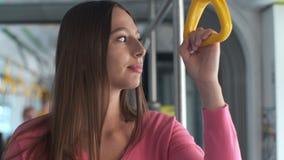 Passeggero della giovane donna che gode del viaggio al trasporto pubblico, stante nel tram moderno stock footage