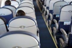 Passeggero dentro l'aeroplano vuoto a metà interno grigio della finestra dell'oblò di problema del salone di volo della cabina immagine stock