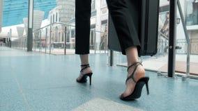 Passeggero femminile giovane all'aeroporto, fine su sulle gambe con i tacchi alti mentre aspettando il suo volo camminante in ter archivi video