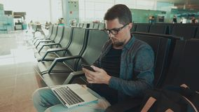 Passeggero maschio che si siedono nel corridoio aspettante in aeroporto e sms mandanti un sms dallo smartphone stock footage
