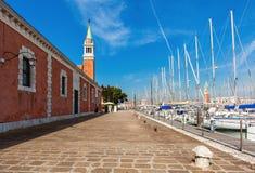 Passeggi lungo il piccolo porticciolo sull'isola di San Giorgio Maggiore Immagine Stock
