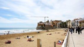 Passeggia e la spiaggia di Sitges con la chiesa nei precedenti Immagini Stock Libere da Diritti