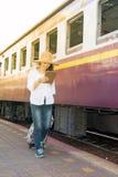 Passeggiata abbastanza asiatica del viaggiatore delle donne ed osservare la compressa la stazione ferroviaria Fotografia Stock