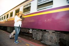 Passeggiata abbastanza asiatica del viaggiatore delle donne ed osservare la compressa la stazione ferroviaria Fotografie Stock