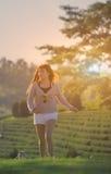 Passeggiata asiatica felice della ragazza su erba nel giorno soleggiato fotografia stock